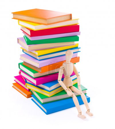Photo for Wooden dummy puppet sitting on the bottom of stacked colorful books - Royalty Free Image