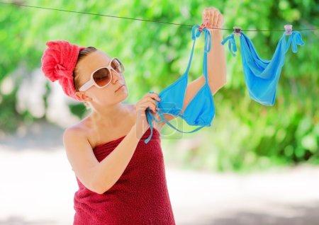 Photo pour Femme dries bikini bleu sur corde à linge. - image libre de droit