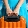 Woman in blue dress holds orange suitcase in hands...