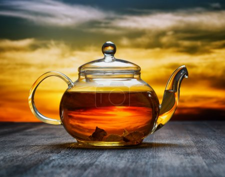 Teapot of fresh tea on sky background....