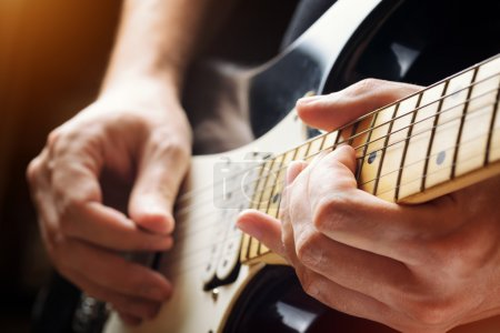 Photo for Man playing guitar on a stage. Musical concert. Close-up view. - Royalty Free Image