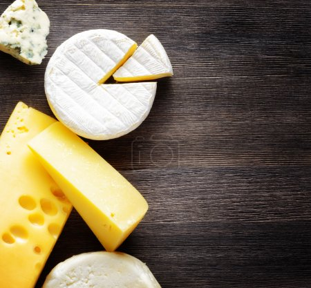 Photo for Different types of cheese on a wooden board. - Royalty Free Image