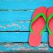 Red ang green flip flop sandals on blue wood...