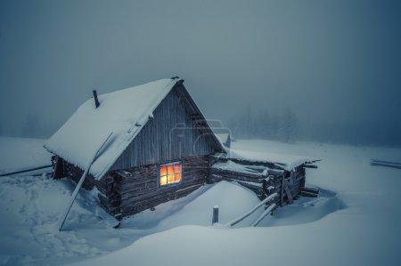 Photo pour Maison en bois dans la forêt d'hiver - image libre de droit