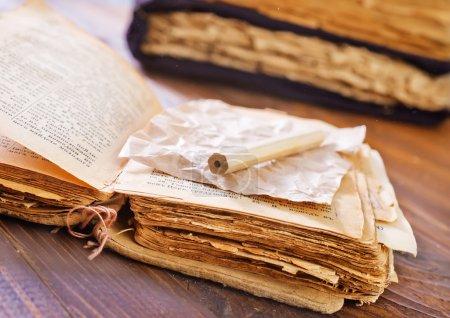 Photo pour Vieux livre avec un crayon sur un bureau en bois - image libre de droit