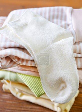 Photo pour Vêtements de bébé sur une table en bois - image libre de droit