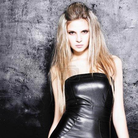 Portrait beautiful woman with elegant black dress on grunge wall background.