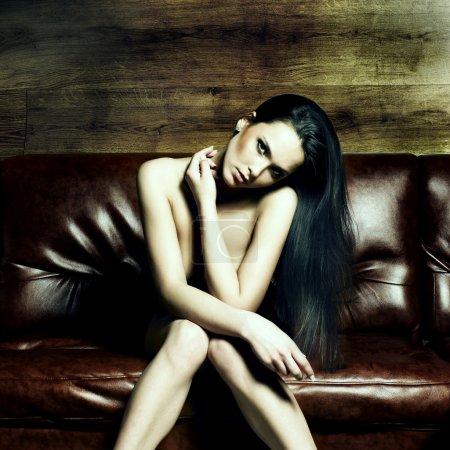 Photo pour Portrait d'une belle jeune femme nue sur un canapé en cuir - image libre de droit