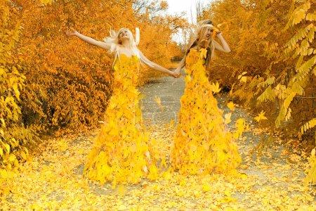 Foto de Dos niñas, vestidas de hojas, habiéndose unido las manos, caminar por un sendero en madera de otoño - Imagen libre de derechos