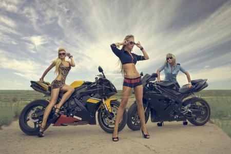 Photo pour Modèle élégant fille séduisante tenues, posant dans des motos sportives, collines de steppe désertique. - image libre de droit