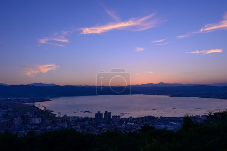 "Photo for Night view of the city of Suwa. The Suwa region is the leading industrial area of Nagano and was once known as ""The Oriental Switzerland"" for its highly developed precision machinery industry. - Royalty Free Image"