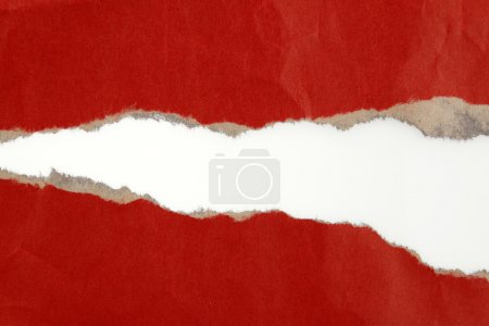 Hole ripped in red paper on plain background...