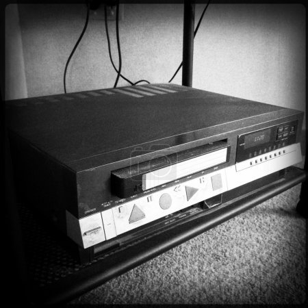 Old VHS video recorder with cassette in slot...