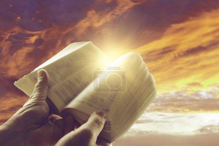 Photo pour Les mains tenant un livre ouvert devant le ciel - image libre de droit