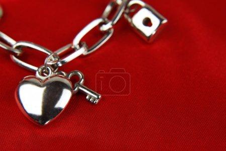 Photo pour Gros plan du coeur et clé sur bracelet à breloques - image libre de droit