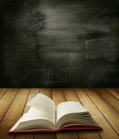 Photo pour Livre ouvert sur table devant le tableau noir - image libre de droit