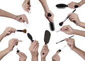 Many hands with make up equipment
