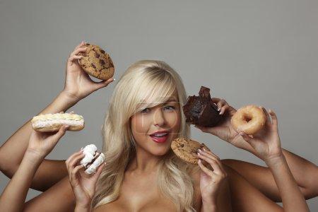 Photo pour Femme sexy entourée de nombreuses mains tenant des gâteaux à la crème avec tant de choix et de tentation va-t-elle oublier son régime alimentaire et se livrer - image libre de droit