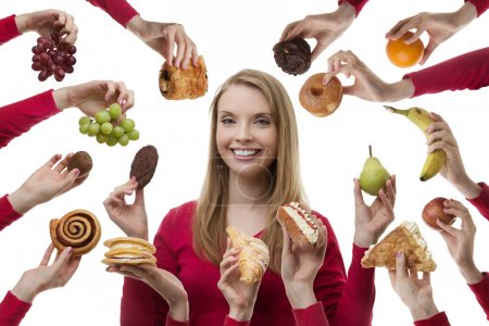 Photo for Young woman surrounded my many cakes and fruits not sure what to eat - Royalty Free Image