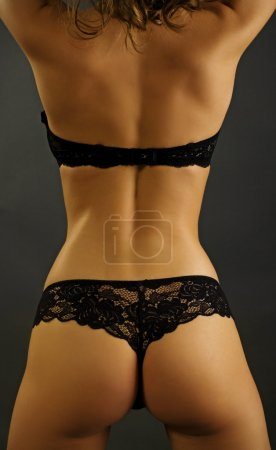 Sexy back of young beautiful blonde in lingerie over dark backgr