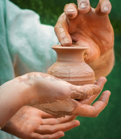 Photo for Close-up of hand holding pottery an jar - Royalty Free Image