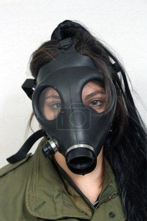 Photo pour Une jeune femme portant un masque à gaz et une veste kaki militaire. - image libre de droit