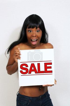 Photo pour Une excité, jolie jeune femme est titulaire d'un signe de la « vente ». - image libre de droit