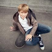 škola teen sedí na skateboardu v blízkosti školy