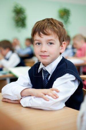 Photo pour Diligent étudiant assis au bureau, salle de classe - image libre de droit