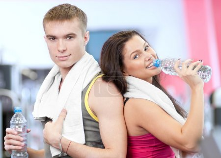 Photo for Man and woman drinking water after sport exercises. Fitness gym. - Royalty Free Image