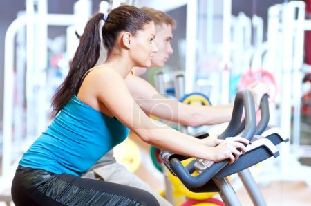 Photo for Group of two in the gym, exercising their legs doing cardio cycling training - Royalty Free Image