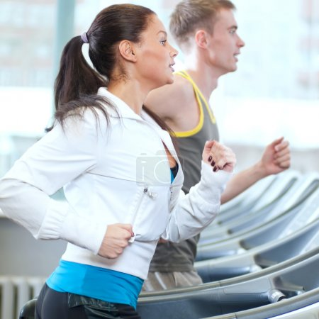 Woman and man at the gym exercising