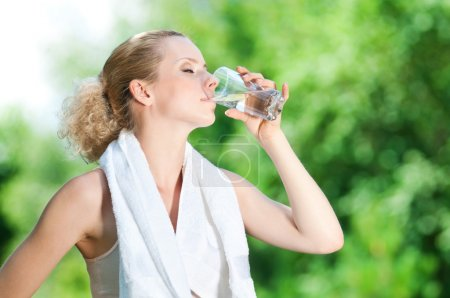 Photo for Young woman drinking water after fitness exercise - Royalty Free Image