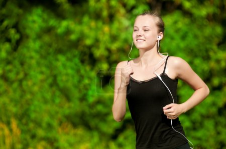 Photo for Beautiful young woman running in green park on sunny summer day - Royalty Free Image