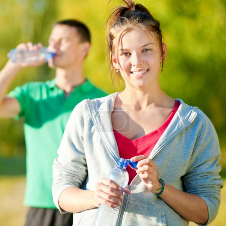 Photo for Man and woman drinking water from bottle after fitness sport exercise - Royalty Free Image