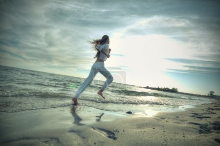 Sporty woman running in sea coast