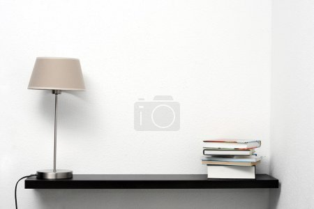 Photo for Bookshelf on the wall with lamp and books - Royalty Free Image