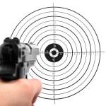 Hand with gun shooting target...