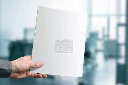 Photo pour Main tenant magazine vierge avec espace de copie au bureau - image libre de droit