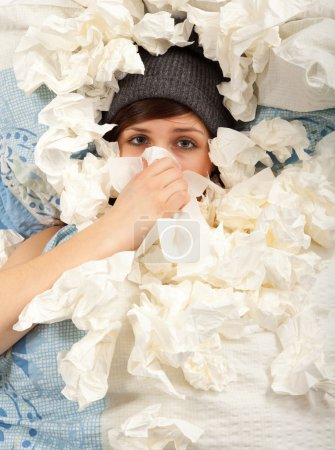 Photo for The young girl is lying sick in bed and blowing her nose - Royalty Free Image