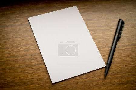 Photo for White paper and pen on wooden board - Royalty Free Image