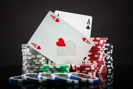 Poker chips and playing cards on black background