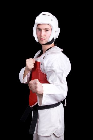 Young man in Taekwondo gear standing against black background
