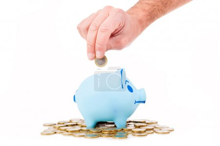 Hand insert coin into the piggy bank, isolated on white
