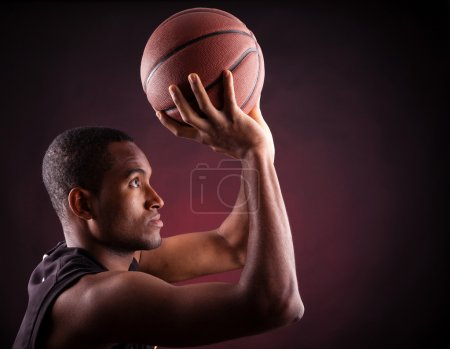 Photo for Portrait of a young male basketball player against black background - Royalty Free Image