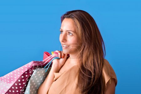 Photo pour Portrait d'une belle jeune femme tenant des sacs à provisions sur fond bleu - image libre de droit