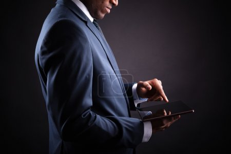 Photo for Businessman working on a digital tablet against black background - Royalty Free Image