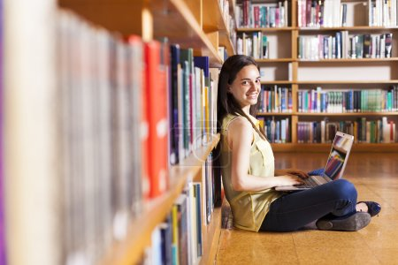 Portrait of a young smiling student using her laptop in a librar