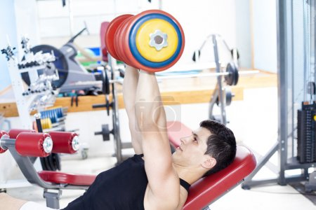 Strong man lifting heavy free weights at the gym