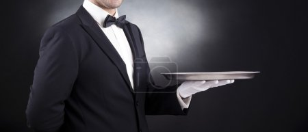 Photo for Waiter holding empty silver tray over black background - Royalty Free Image